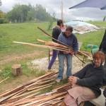 Une stagiaire apporte de longues baguettes de bois pour alimenter l'alandier.