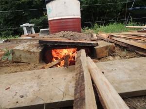 On enfourne le bois au fur et à mesure dans l'alandier pour monter en température.