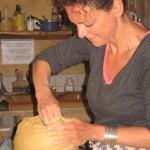 Pascale monte plusieurs colombins avant de les lisser pour les faire adhérer entre eux et à la base du vase.