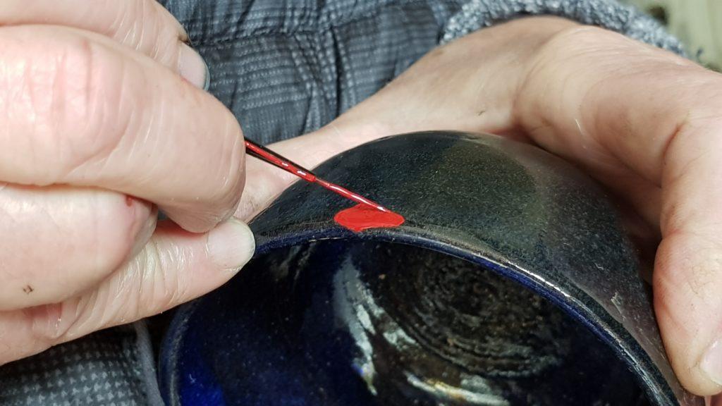 Kintsugi. Pose de la laque rouge, support de la poudre d'or